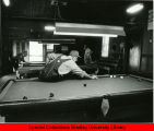Man sitting on pool table  to get a shot