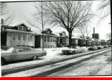 Snowy residential street with cars