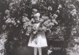 Girl holding flowers in front of flowering bush