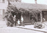 Man, woman, and child in front of house