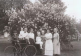 Group portrait in front of bush with bicycle