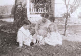 Woman and children sitting in grass with kittens