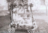 Boy, girl, and kittens in decorated wagon