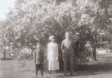 Three children in front of shrub