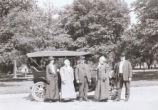 Group standing in front of automobile