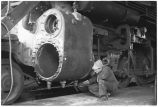 Locomotive being repaired in roundhouse