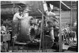 Working on locomotive at repair shops, W. Burlington, Iowa