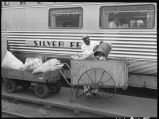 Worker emptying trash from Zephyr coach, 14th Street passenger yards, Chicago, May 1948