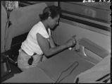 Worker cleaning ashtrays in Zephyr coach, 14th Street passenger yards, Chicago, May 1948