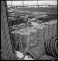 Aurora-Burlington storehouse-Workman prepares fasten chain on wheel, which will then be moved by giant