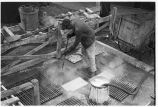Worker steam-cleaning floor mats, 14th Street passenger yards, Chicago, May 1948