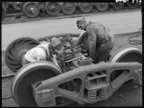 Working on truck of railroad car-Car repair tracks-Galesburg, Ill.