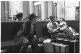 Man with infant talking to fellow traveler in waiting room, Union Station, Chicago, May 1948