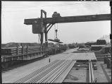 Electromagnetic crane lowering rails onto flatcar-Material yards, Havelock, Nebraska