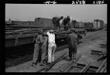 Workers unloading rail sections from flat car, Western Avenue rail yards, Chicago, 1948