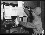 Railroad fireman reading orders in enginemen's room,14th Street passenger yards, Chicago, May 1948