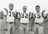 No. 78, no. 32, and no. 55 on the football team standing on the field.