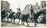 A few Native American men riding on horses wearing feather headpieces.