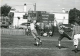 Two football players from opposite teams going for the ball. (The ball is about to go into the...