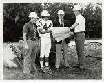 Group picture of Coach Dan McCarrell, football player and two other men all wearing hard hats...