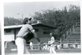 A North Park baseball player throwing a baseball in the infield to warm up with other players in...