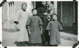 Pastor Wu standing outside with his wife and three children in Kingmen