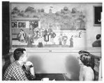 Two students sitting in a booth at the Student Snack Lounge looking at a mural of Old Main at...