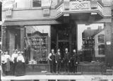 Four men and four women standing in front of the mission friends office at 144 Oaks St. Chicago