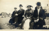 E.G. Hjerpe with group of three sitting in coats