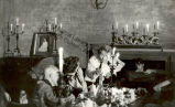 Persons in Dining Room with Candelabras