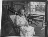 Woman seated on porch with loom