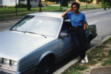Mari Evans posing beside a car