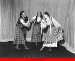 Women in folk costumes dancing on stage