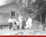 Children and a woman posing outside of cabin
