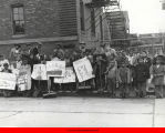Children holding brooms and signs in front of Henry Booth House