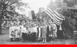 Boys and girls posing with banner and American flag