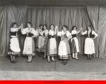 Young women in Bohemian folk costumes in dancing formation