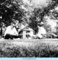 Adults sitting on lawn in front of Smith Cottage