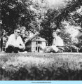 Adults, looking up, sitting on lawn in front of Smith Cottage