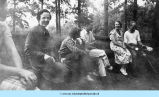 Men and women sitting on log