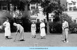 Women playing croquet