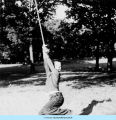 Boy hanging from rope swing at Camp French