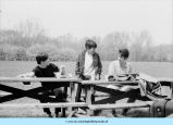 Three boys sitting at picnic table