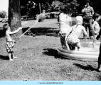 Children being sprayed in wading pool