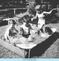 Standing girl and two boys playing in wading pool