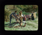 Picnics and Recreation Activities – [Man Sawing Wood Near Pioneer Dressed Women]