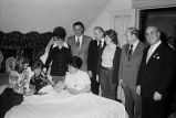Congressman Frank Annunzio with others visiting older woman