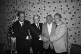 Congressman Frank Annunzio shaking hands with three others