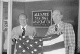Annunzio holds flag with Chester Wiktorski outside the Alliance Savings and Loan Association