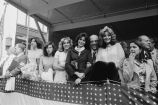 Congressman Frank Annunzio, a Parade Queen and others stand on a parade reviewing stand
